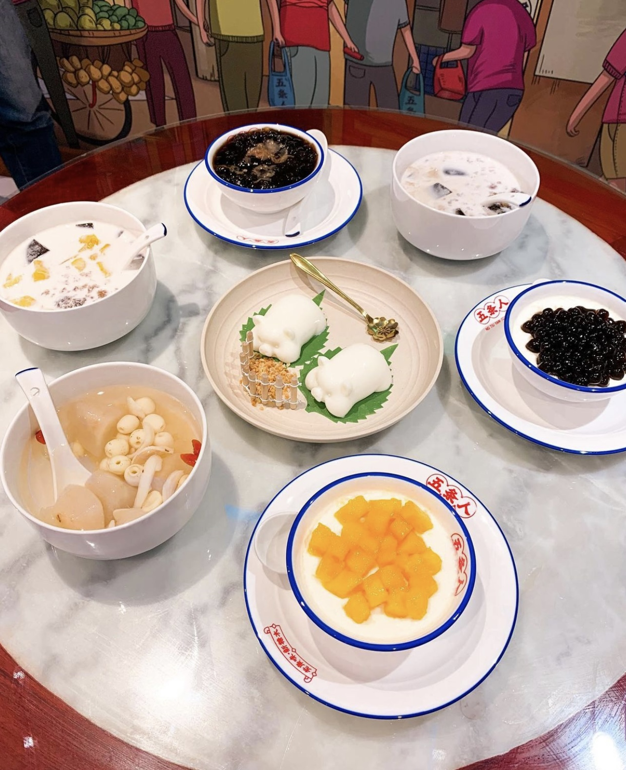 Round table, with table 6 bowls of assorted Cantonese desserts and a coconut jelly pig pudding in the centre.