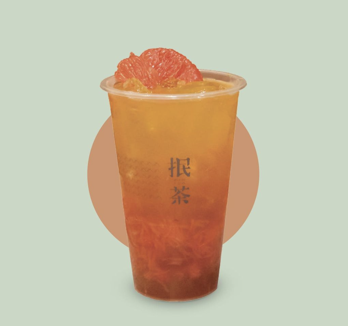 Cup of grapefruit flavoured and coloured green tea with ice and real grapefruit at the top