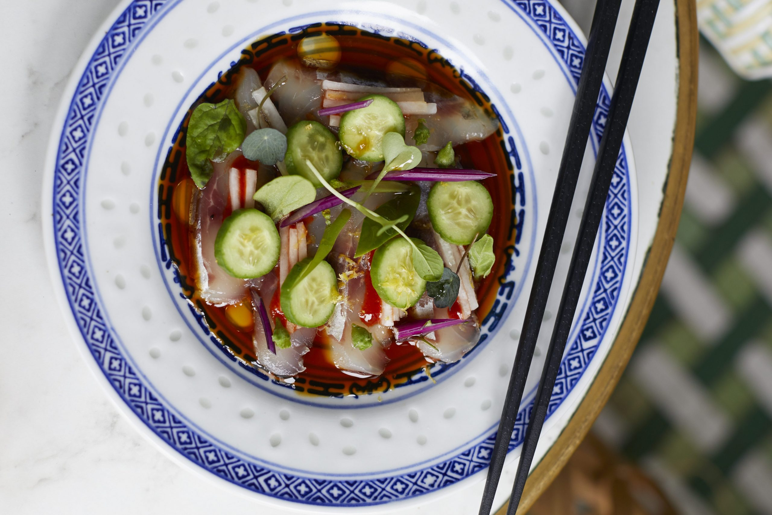 Thinly sliced cured mullet fish with sliced cucumbers.