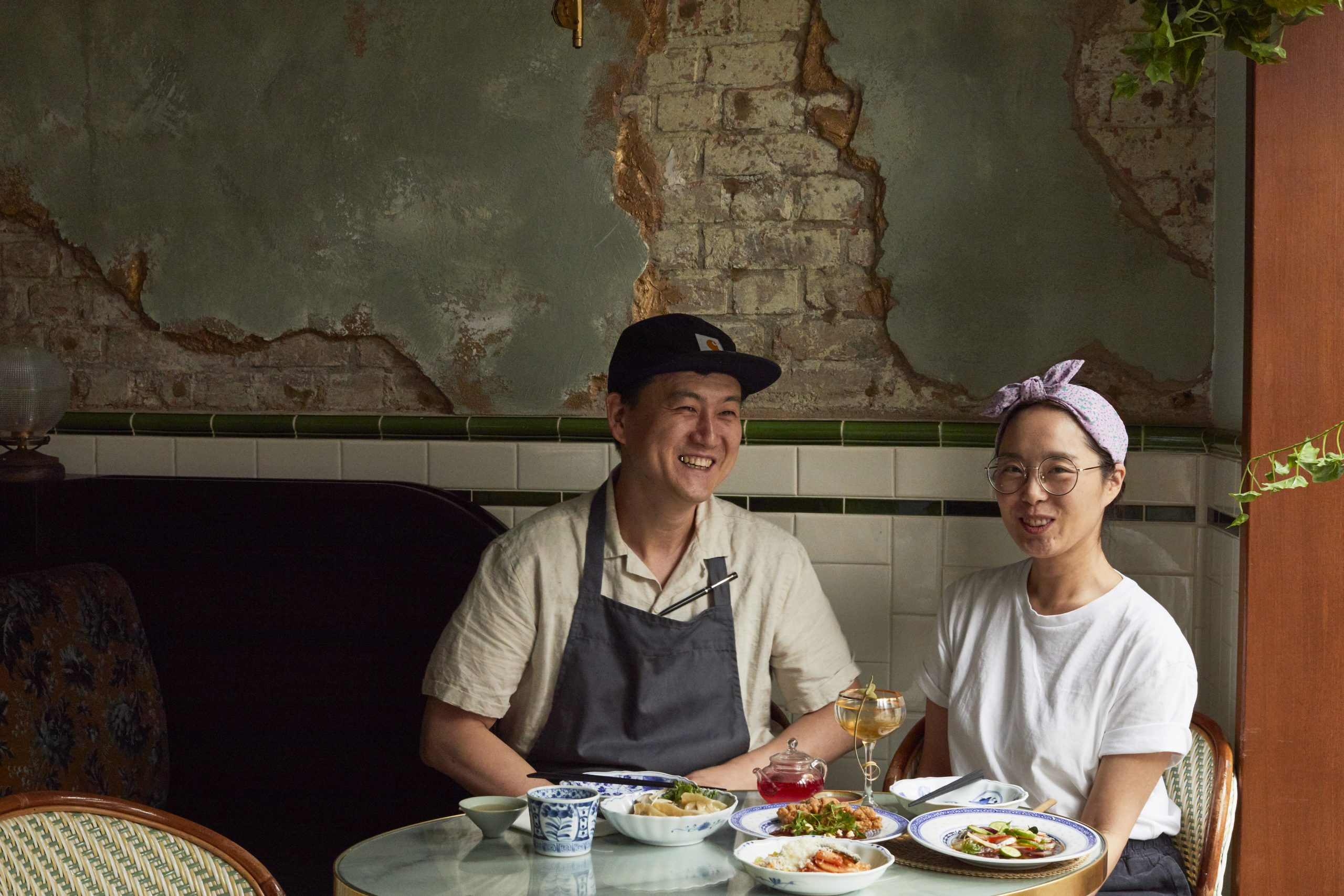 Chefs Joo Won (left) and Sujin (right) sitting down by a table of their Korean dishes.