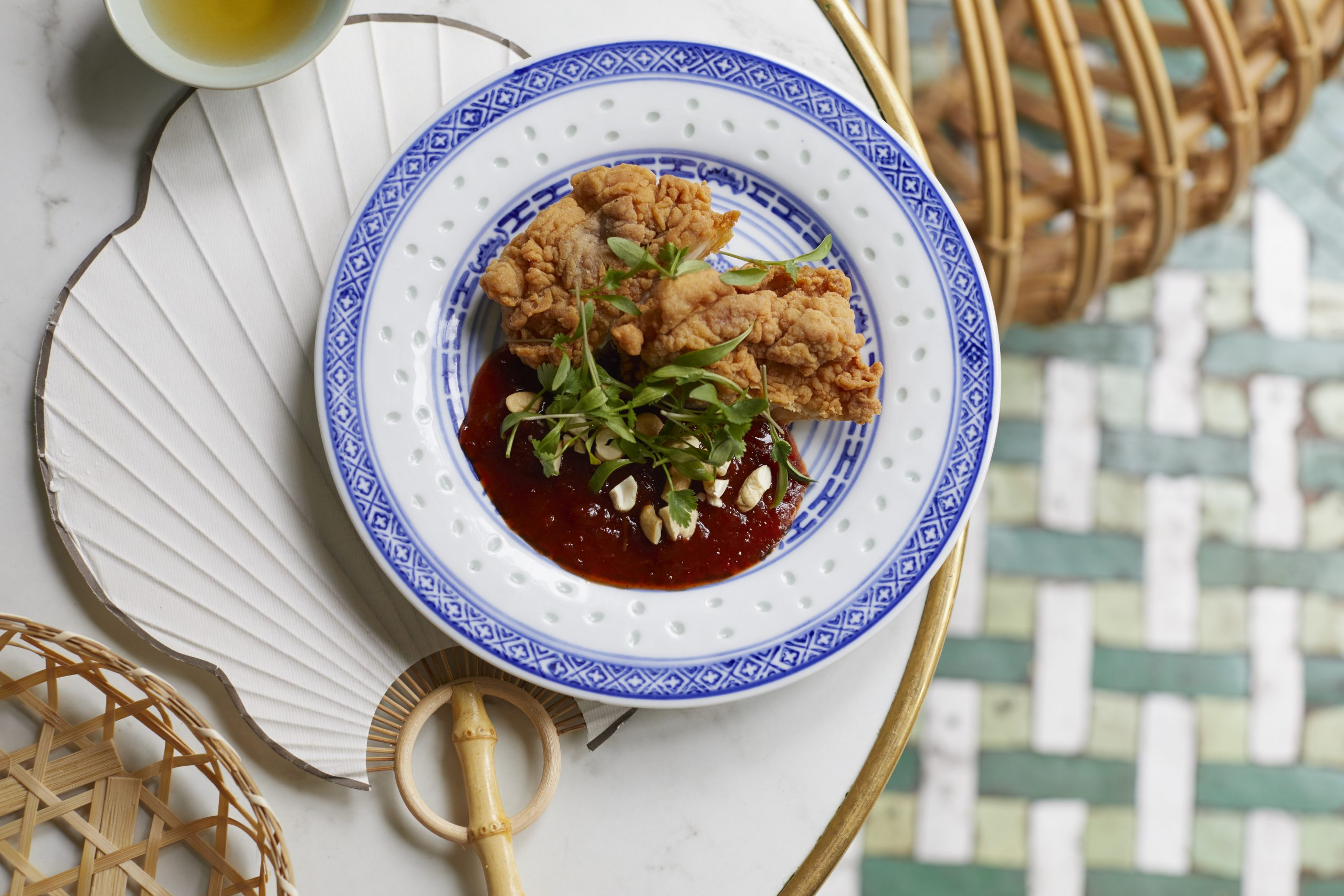 Deep fried chicken on a china plate, topped with cashews and coriander.