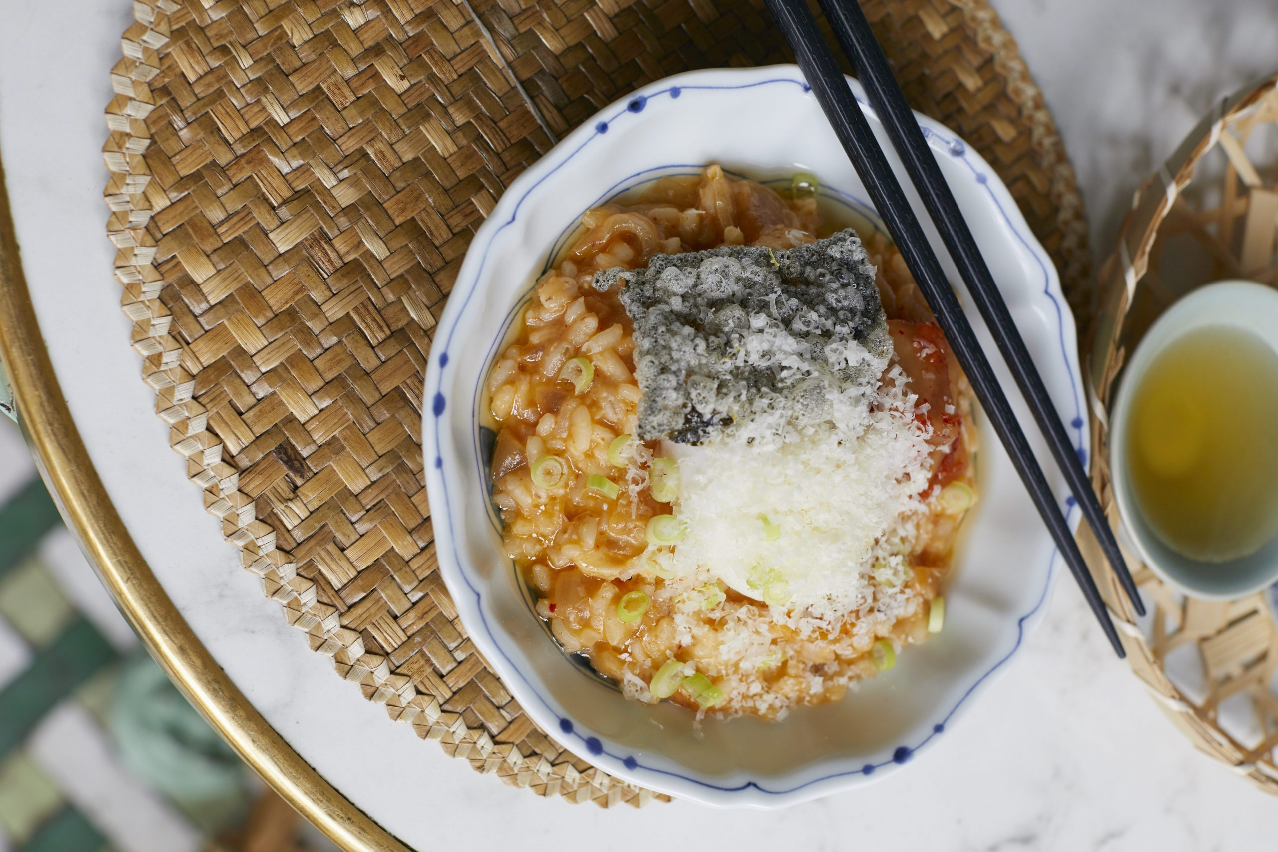 A bowl of risotto with kimchi, poached egg and crispy deep fried seaweed.
