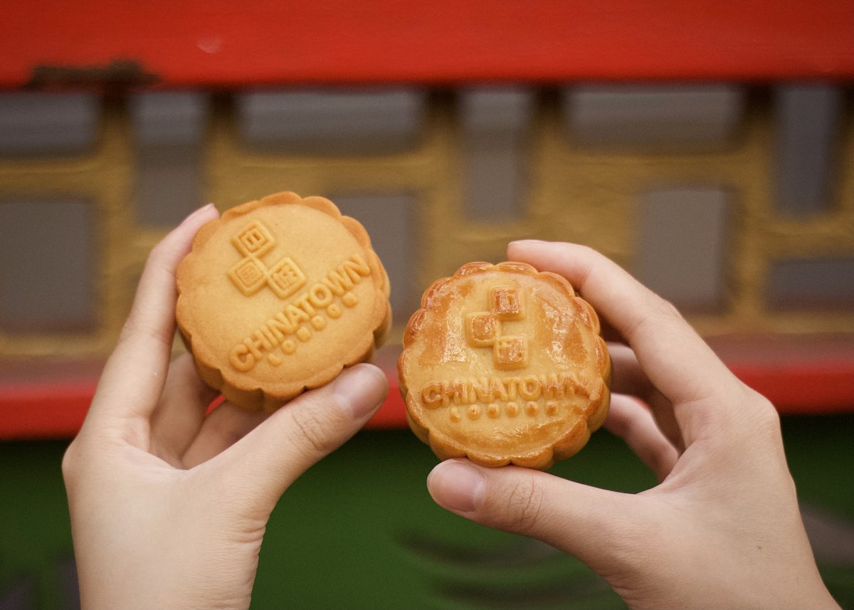A photo showing a close-up of a mooncake pastry in each hand